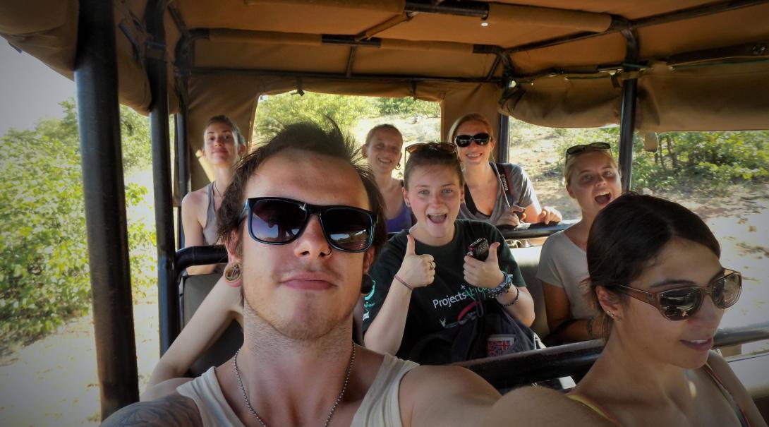 En grupp ungdomsvolontärer åker safarijeep i bushen i Botswana.